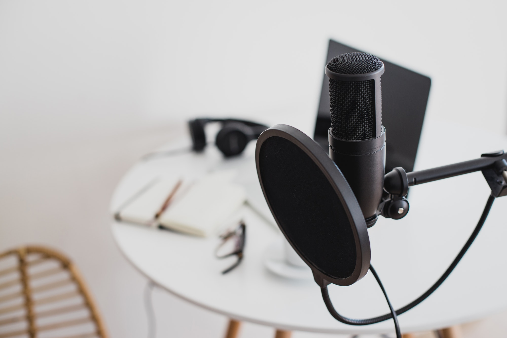 Items for recording online podcast: studio microphone, laptop and earphones.
