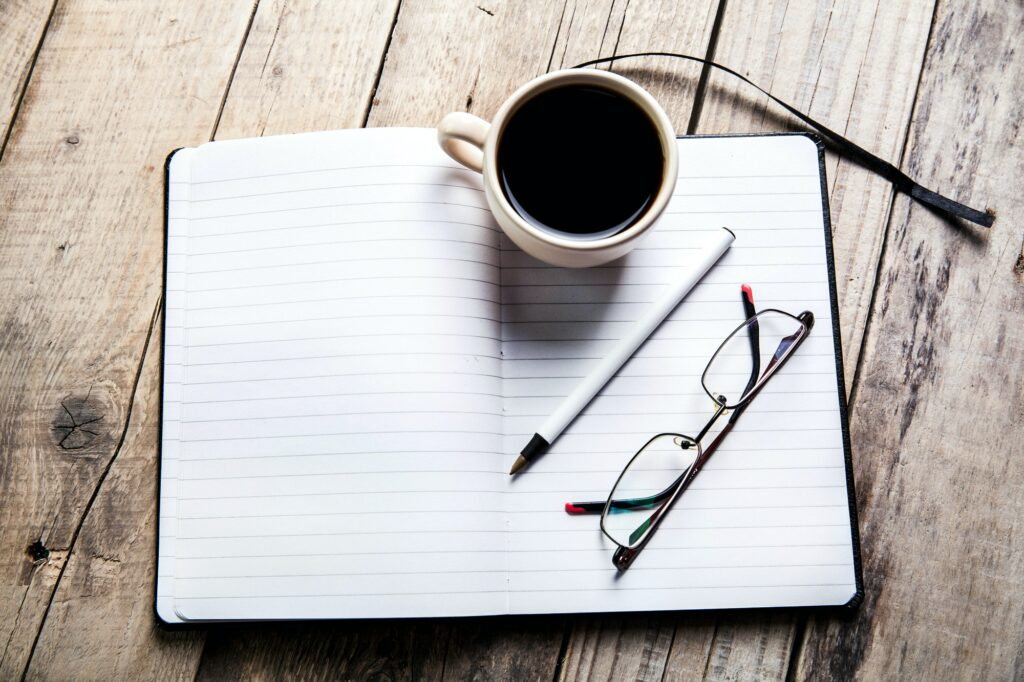 glasses on notebook with pen and cup
