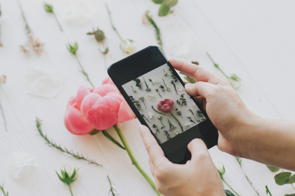 Hands holding phone and taking photo of stylish spring flowers flat lay. Blogging and social media