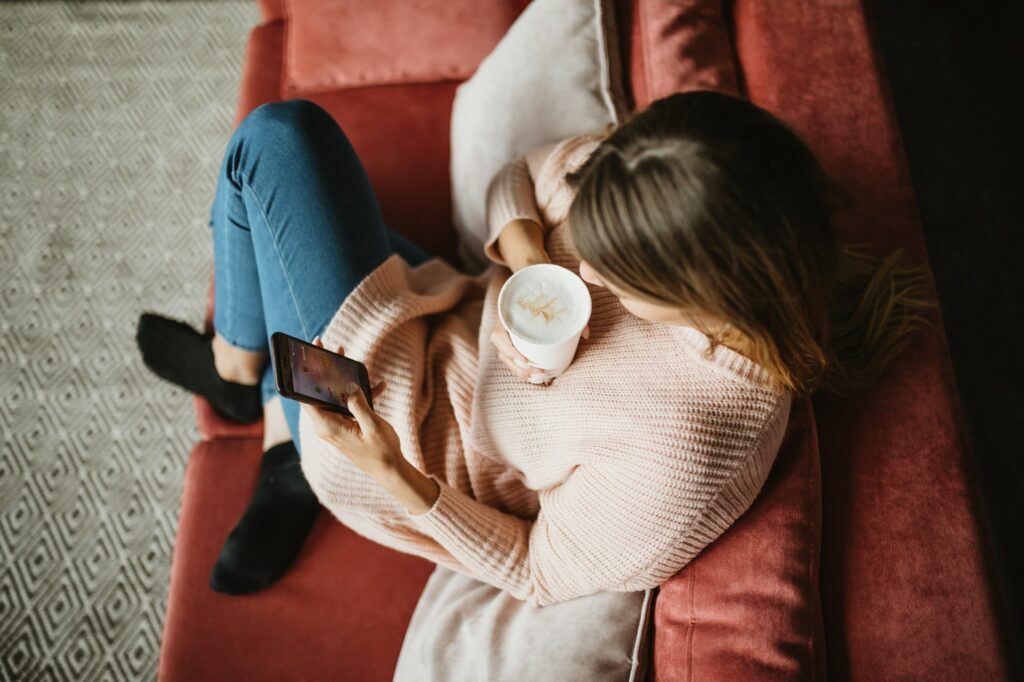 Woman using telephone at home. Social media. Relaxing in couch.